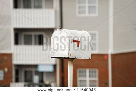 close up on old fashioned mailbox in residential area with blurred building as background
