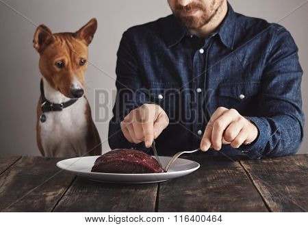 Man Cuts Piece Of Steak For His Dog