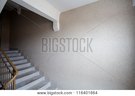 Part Of A Gray Staircase With Wooden Railing, Brown Wall