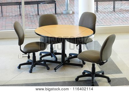 table and chairs in college lobby