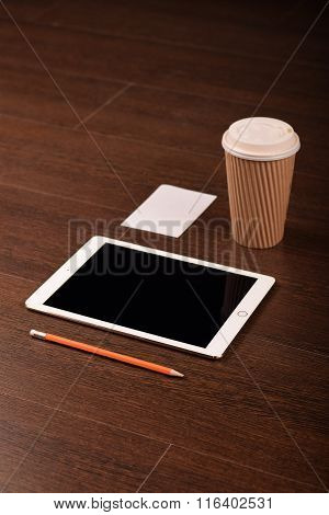 Workspace mock up. Tablet, coffee, blank card, succulent on the wooden table, pencil