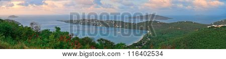 Virgin Islands St Thomas sunset panorama mountain view with colorful cloud, buildings and beach coastline.