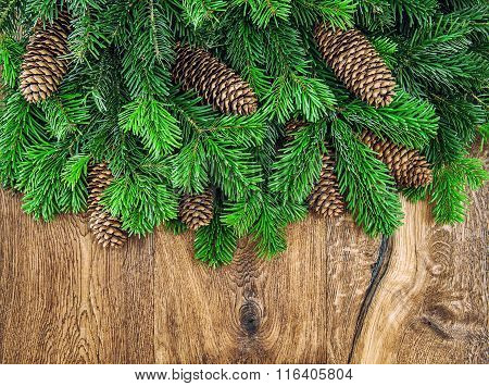Christmas Tree Branches With Cones On Wooden Background