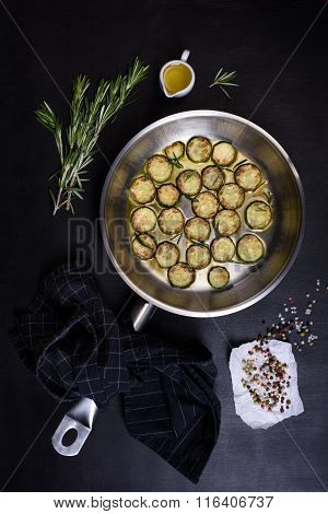 Vegetarian dish, zucchini fried with rosemary in a pan on dark wooden background. Top view.