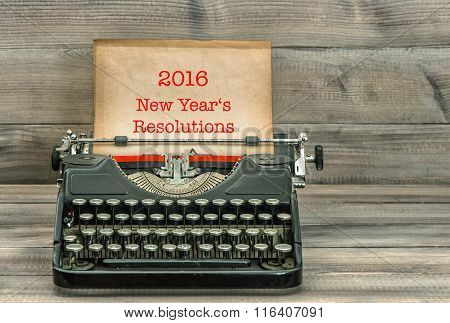 Antique typewriter with grungy paper page on wooden table. Sample text 2016 New Year's Resolutions. Retro style toned picture