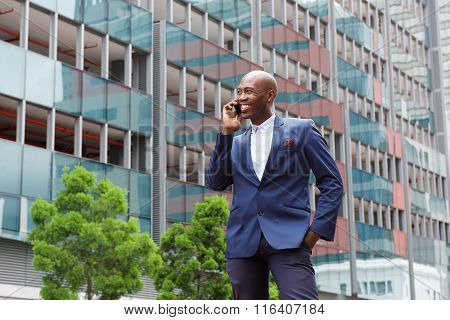 African Businessman Talking On Mobile Phone In The City Street