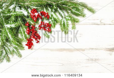 Evergreen Tree Branch With Red Berries On Wooden Background