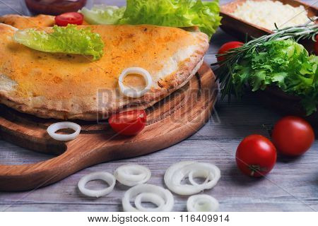 Closed Pizza Calzone On A Light Wooden Background