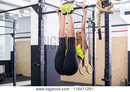 Fit girl training abs by raising legs on a horisontal bar. Fitness woman workout doing exercises at