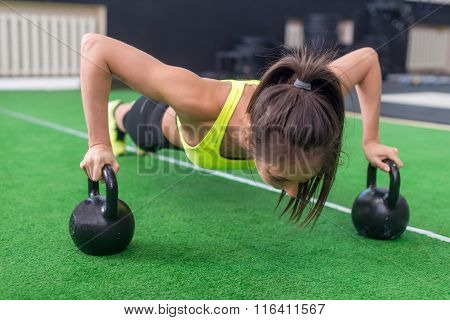 Fit woman young doing push ups exercise with dumbbells in the gym