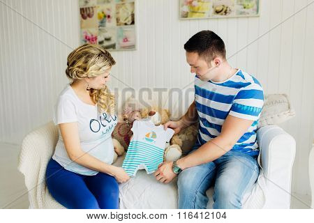 Young Pregnant Woman With Husband On White Sofa In Room  Looking At Baby Clothes.