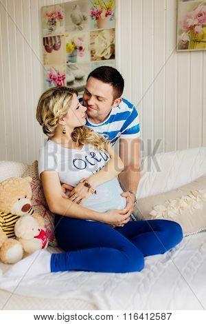 Pregnant Beautiful Woman With Her Handsome Husband Sweetly Resting Indoors On White Sofa.