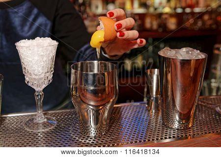 Bartender is adding egg yolk to the glass