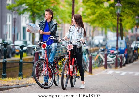 Happy tourists sightseeing city with map on bikes