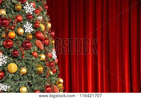 Christmas tree against red drapery