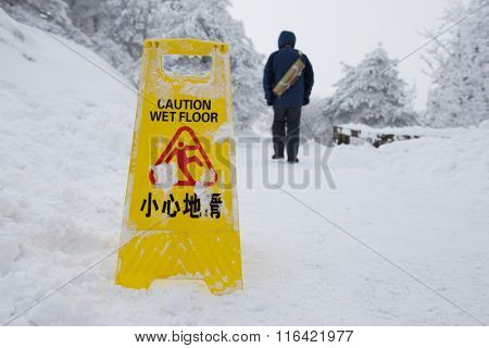 warning caution sign board on snow floor on hill