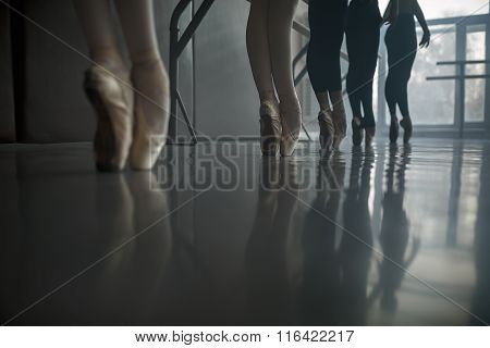 Ballet dancers stands by the ballet barre.