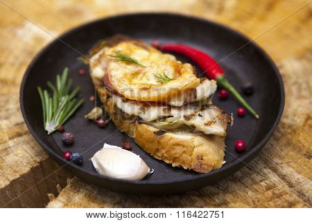 Home baked hot sandwich with chicken cheese, onion, chile pepper, garlic  on a cast-iron pan on a wooden background