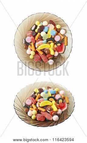 Glass plate full of candies isolated