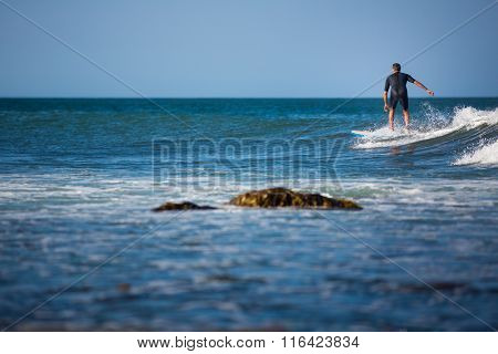 Young boy surfing the wave in a sunny day