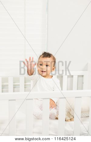 Cute baby greeting in the crib
