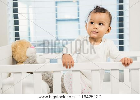 Cute baby in the crib looking around