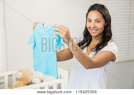 Smiling brunette holding baby tshirt in bedroom