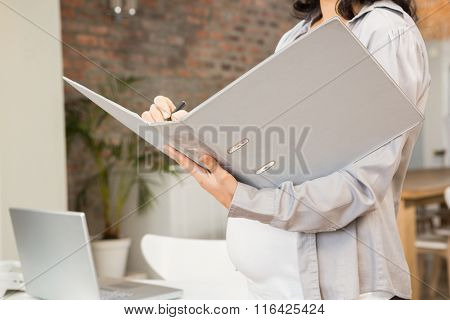 Mid section of pregnant woman holding folder
