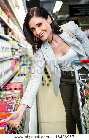 Smiling woman picking yoghurt in supermarket