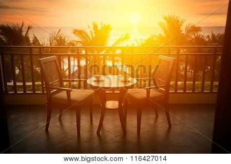 romantic table on terrace, sunset in background