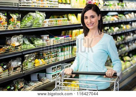 Smiling woman pushing trolley in aisle in supermarket