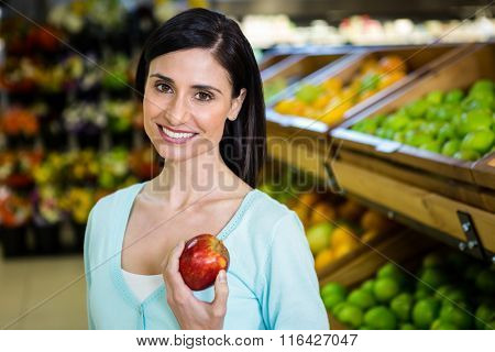 Portrait of a smiling woman picking apple in supermarket