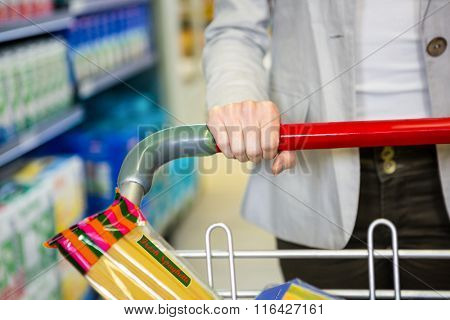 Cropped image of woman pushing trolley in aisle in supermarket