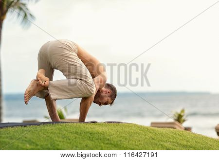 Young man doing yoga on the beach near the ocean