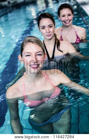 Female fitness class doing aqua aerobics in swimming pool