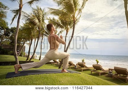 Yoga man at tropical beach doing yoga exercise