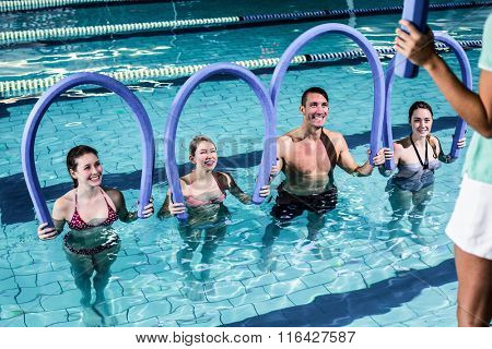Fit group doing aerobical excercises in swimming pool