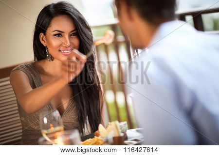 Lovely girl feeding her boyfriend on romantic dinner
