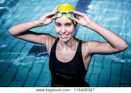 Smiling swimmer woman holding her swimming glasses in swimming pool