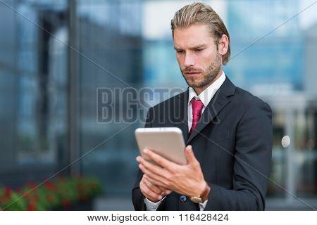 Portrait of a businessman using his tablet
