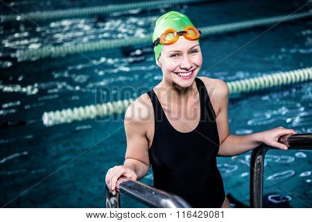 Smiling swimmer woman getting out of the swimming pool wearing swimming hat