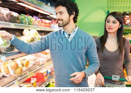 Smiling young couple shopping in a supermarket