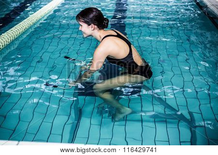 Side view of woman cycling in the pool