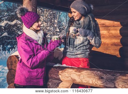 Two girlfriends spending winter holiday on mountain cottage.