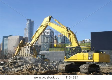 Backhoe Working With A City In The Background