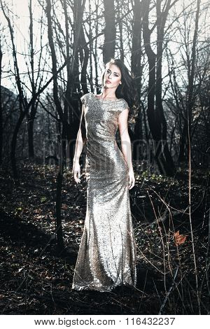 beautiful young woman in elegant glittering  dress  in wood full body shot