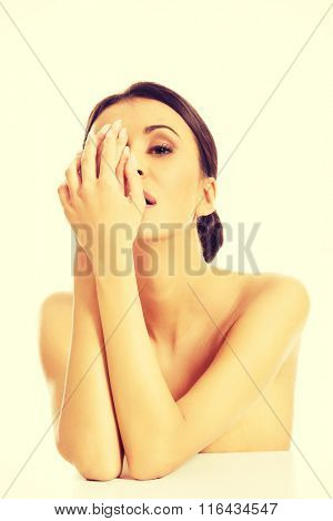 Topless woman covering one eye with hand