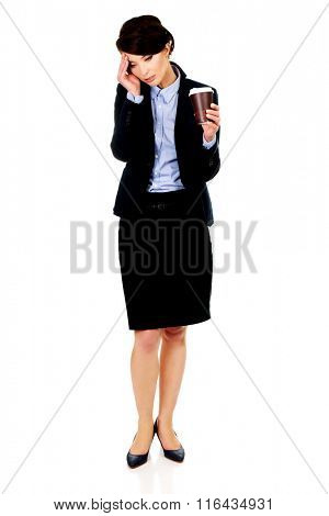 Tired businesswoman holding a cup of coffee.