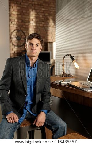 Confident businessman sitting at desk, looking at camera.