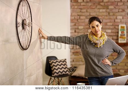 Confident young woman leaning against wall at retro home, smiling, looking at camera.